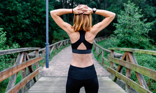 Unrecognizable sportswoman doing stretching arms outdoors