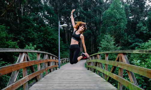 Happy athlete woman jumping outdoors