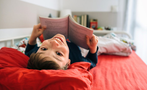 Boy looking camera while reading a book