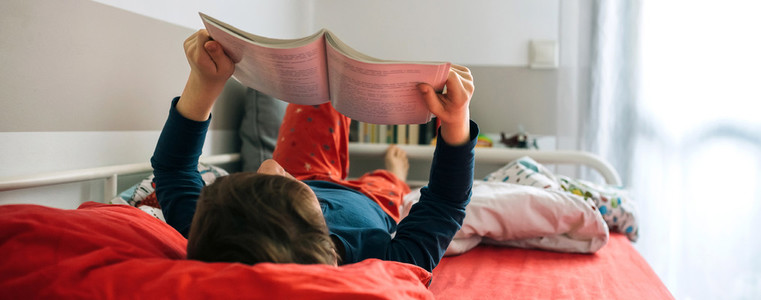 Boy reading on his bed