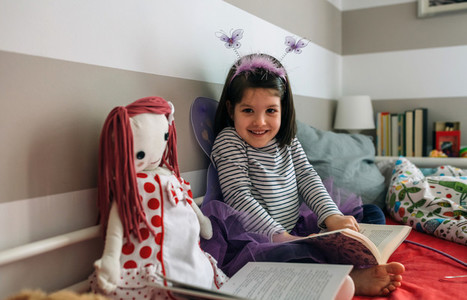 Girl disguised as a butterfly reading with her doll