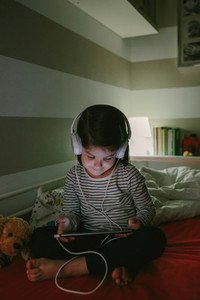 Girl with headphones looking at the tablet