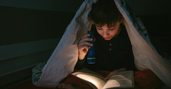 Boy reading with a flashlight