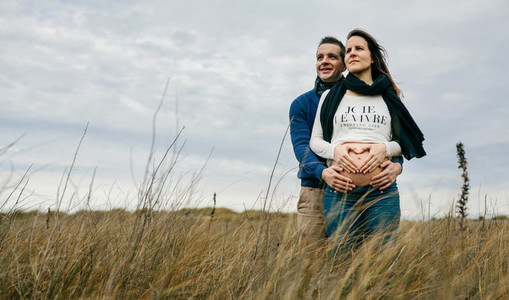 Pregnant making heart with hands on naked belly with partner