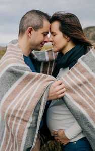 Pregnant with husband covered with a blanket