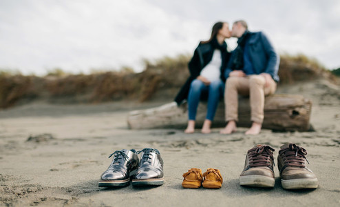 Family shoes in the sand with couple kissing