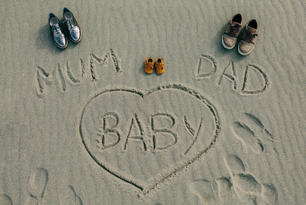 Mum  dad and baby written on the sand of the beach