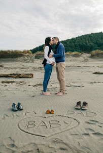 Mum dad and baby written on the sand with the parents kissing behind