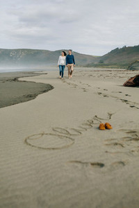 Parents walking with baby name Oliver written in the sand