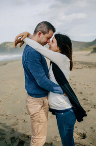 Pregnant woman hugging partner on the beach