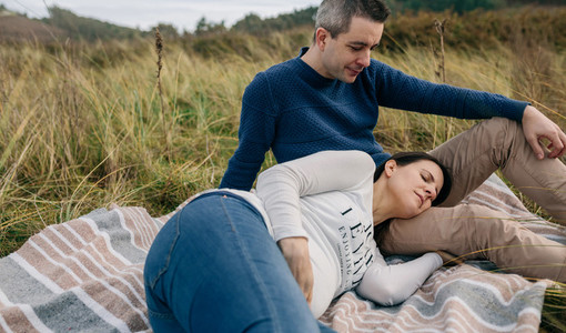 Man looking his pregnant woman resting on the grass