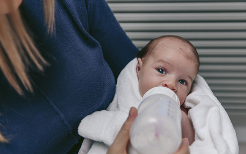 Baby taking feeding bottle