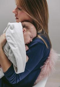 Mother hugging her sleeping baby girl