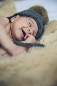 Baby girl with pompom hat sleeping and laughing