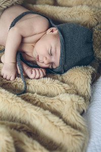 Baby girl with pompom hat sleeping