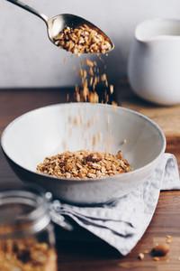 Hand sprinkles baked granola in a ceramic bowl  Healthy vegetarian breakfast