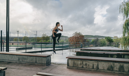 Girl jumping on benches doing training