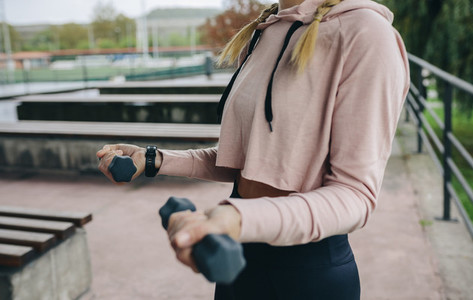 Girl training with dumbbells outdoors