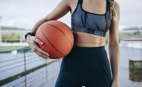 Sportswoman posing with a basketball