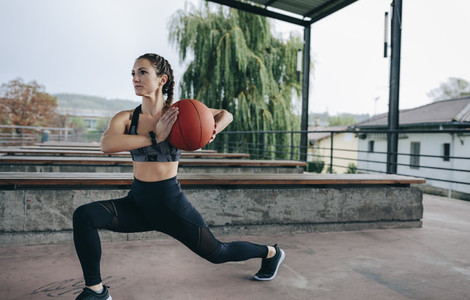 Sportswoman doing stride exercises with basketball