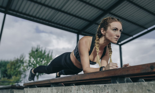 Sportswoman doing plank on a bench