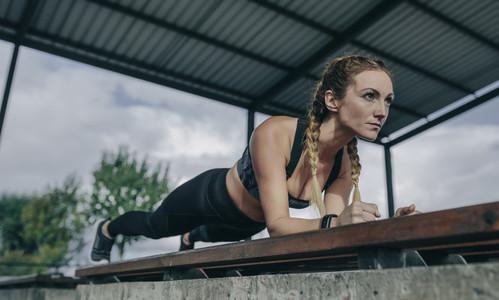Sportswoman doing plank on a bench