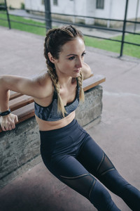 Sportswoman doing arm exercises on a bench