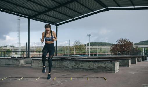 Sportswoman jumping on an agility ladder