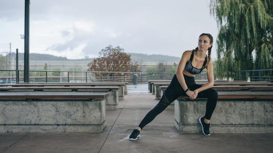 Sportswoman posing sitting on a bench