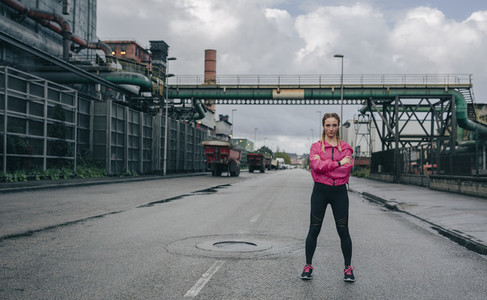 Sportswoman posing arms crossed in an industrial zone
