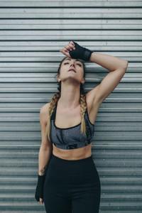 Sportswoman resting on a metal wall
