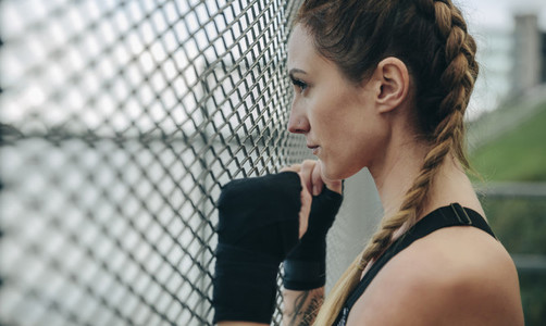 Sportswoman looking through a fence