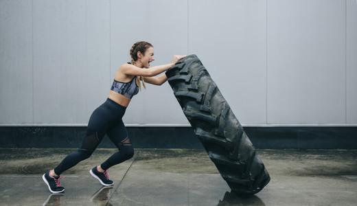 Sportswoman doing cross training lifting a tire