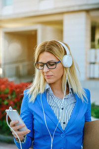 Businesswoman with headphones looking mobile