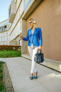 Businesswoman with headphones and mobile