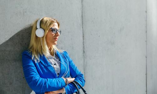 Businesswoman with headphones posing