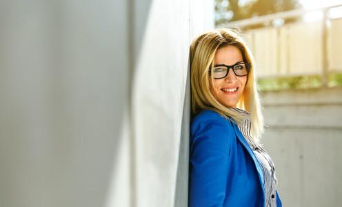 Businesswoman posing on concrete wall