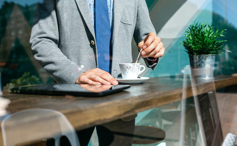 Unrecognizable businessman stirring coffee