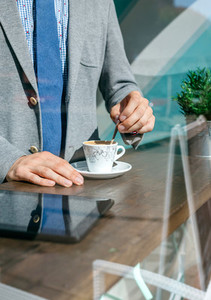 Unrecognizable businessman stirring coffee