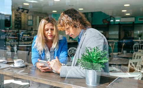 Businesswoman showing phone to coworker
