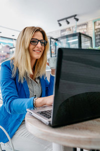 Woman drinking coffee and working with the laptop