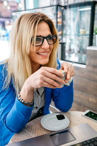 Woman drinking coffee and using the laptop
