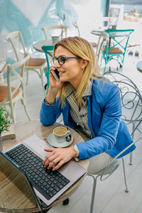 Woman talking on phone with laptop