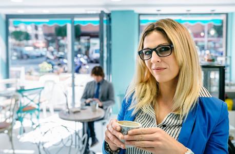 Woman posing holding a coffee