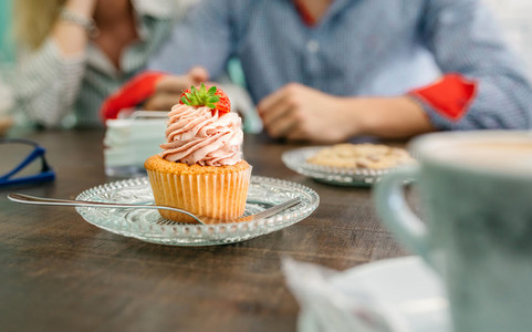 Cupcake with couple holding hands in background