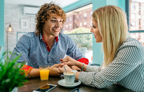 Couple holding hands at a cafe