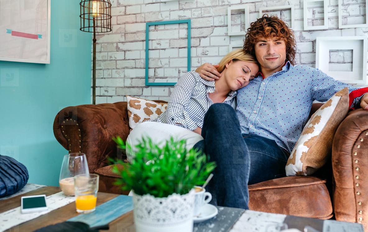 Couple hugging on a sofa