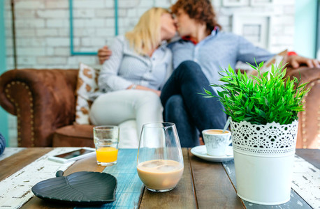 Drinks on a coffee table with a couple kissing