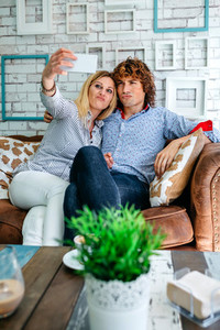 Couple taking selfie on a sofa