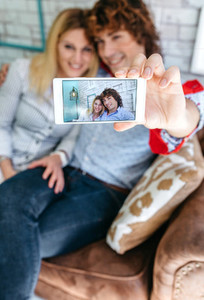 Top view of couple taking selfie on a sofa